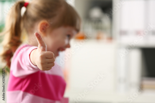Fotografiet Little girl show approve or OK sign with her arm closeup