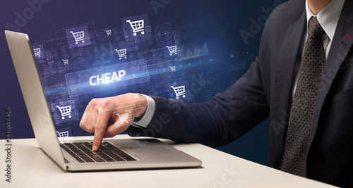 Fotomural Businessman working on laptop with CHEAP inscription, online shopping concept