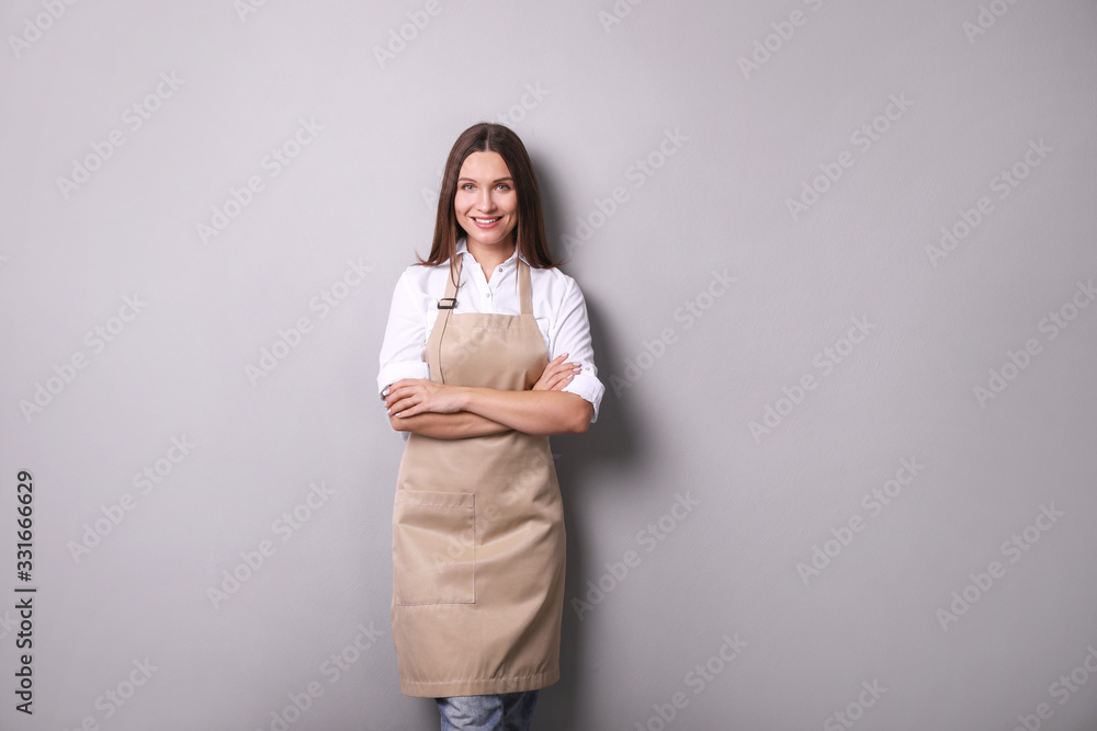 Fototapeta Young woman in an apron on a gray background.