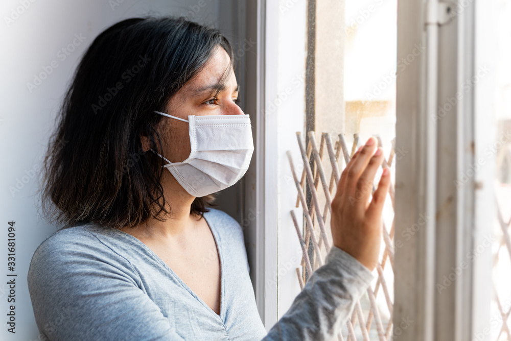 Fototapeta portrait of young woman infected with corona virus with face mask looking out of window while in quarantine with sad and worried expression due to isolation