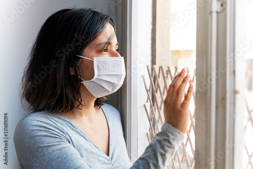 Leinwand Poster portrait of young woman infected with corona virus with face mask looking out of
