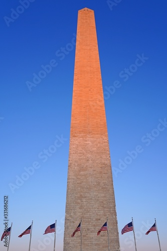 View of the landmark Washington Monument obelisk in Washington, DC with an American flag