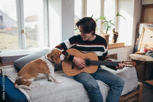 Vászonkép young man playing guitar at home