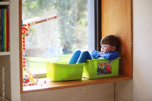 Cuadros en Lienzo Ein vierjähriger Junge sitzt gelangweilt in seinem Zimmer am 18
