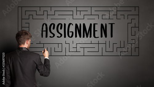 businessman drawing maze with ASSIGNMENT inscription, business education concept Wallpaper Mural