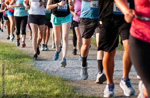 Fotografía Legs of runners on a dirt path running a 5K race