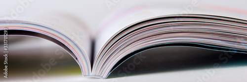 Fototapeta Colorful pages of an open magazine, close up. Selective focus. obraz