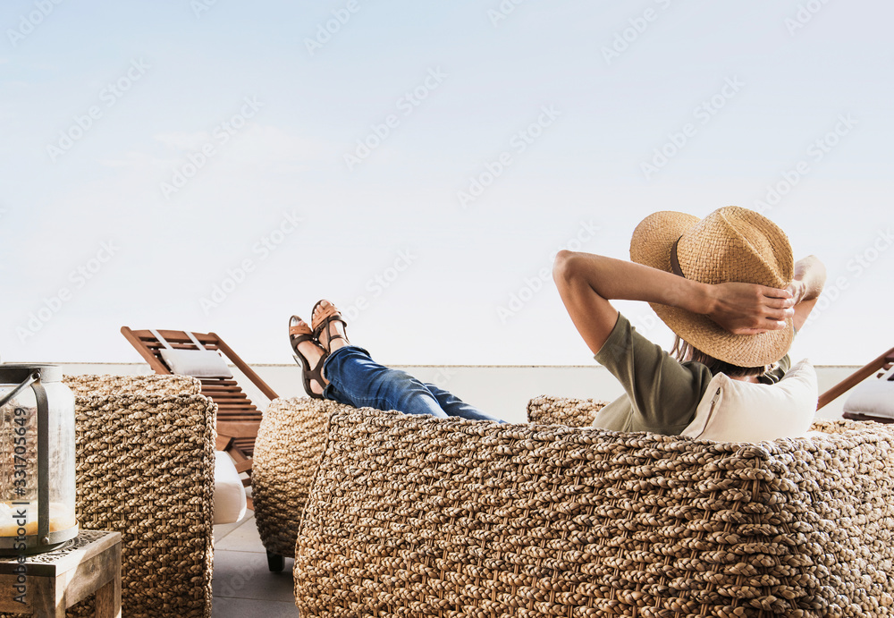 Fototapeta Young woman resting on terrace at home, Beautiful girl enjoying life, Vacations and summer fun concept