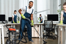 Smiling African American Cleaner Vacuuming Floor Near Team Of Multicultural Colleagues