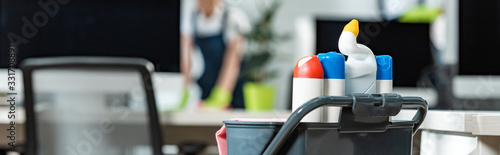 Fototapeta panoramic shot of cart with different cleaning supplies used by cleaning company