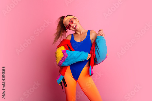 Fototapeta Back in time 90s 80s. Stylish girl in retro jacket and vintage aerobic body jump suit dancing, fashion trends, entertainment, heat in summer. Happy and positive. Horizontal, copy space. obraz