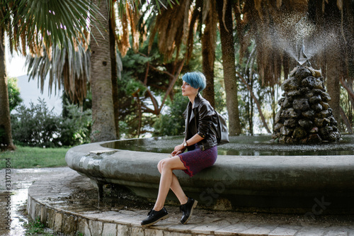 Fototapety, obrazy: A woman in a black leather jacket, dress and shoes sits on the edge of an old fountain