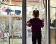 The child alone stands on the windowsill. Baby safety at home. Cute girl looks out the open window.