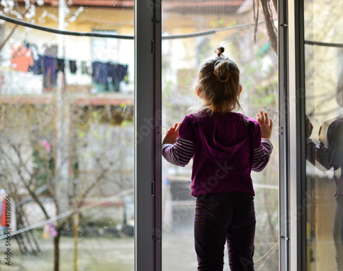 Obraz The child alone stands on the windowsill. Baby safety at home. Cute girl looks out the open window. - fototapety do salonu