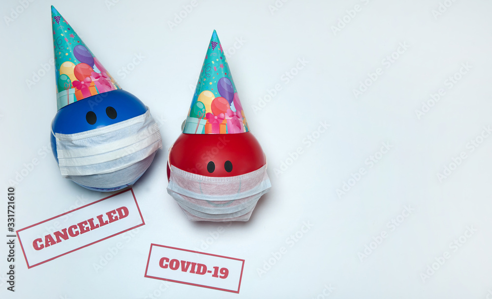 Fototapeta The concept of canceling celebrations due to the Covid-19 coronavirus pandemic. Balloons in party caps and medical masks, signs warning of quarantine on a white background. Free space.