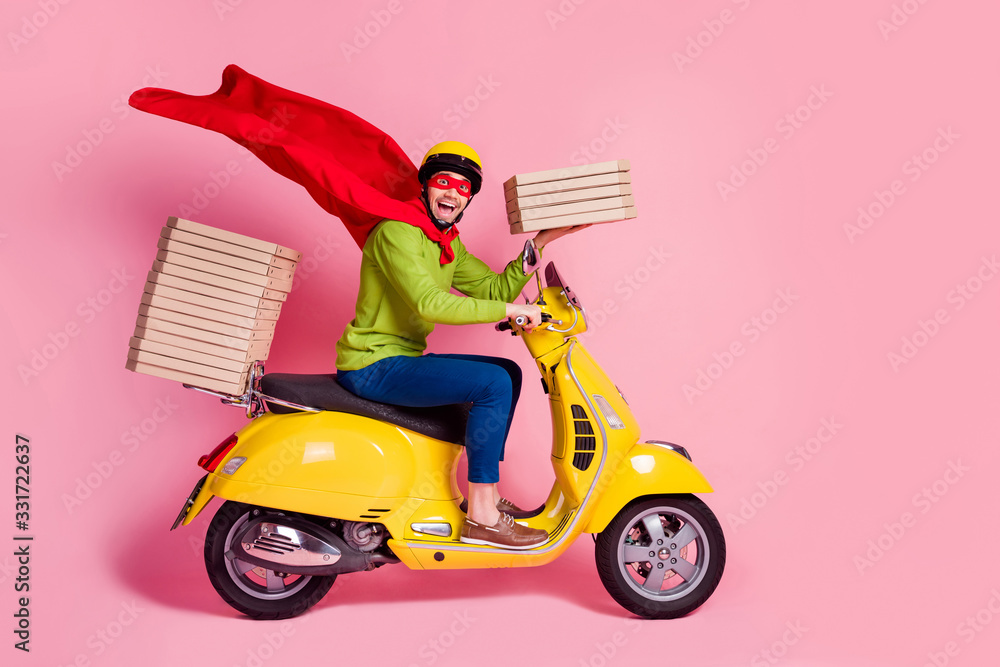 Fototapeta Profile side view of his he nice attractive funky cheerful cheery ecstatic guy driving moped fast speed wearing cape service order client hurry rush isolated over pink pastel color background