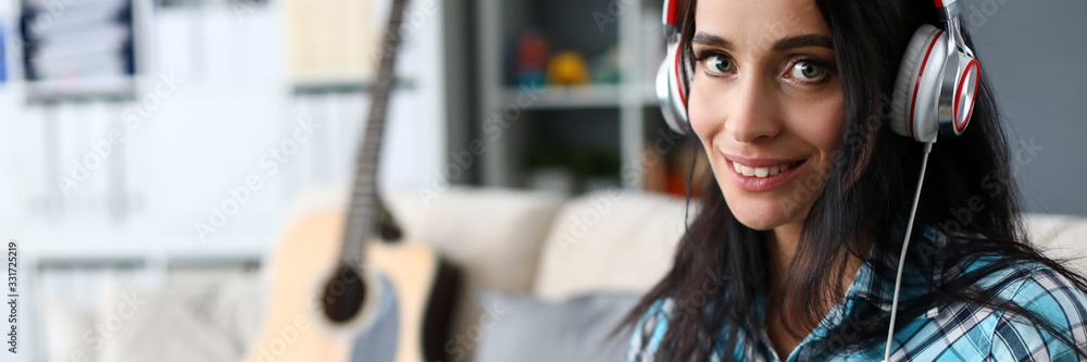 Fototapeta Portrait of smiling lady in modern headset playing synthesizer by notes. Lovely woman in stylish casual shirt looking at camera with happiness and tenderness. Art concept