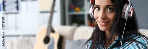 Obraz na plátně Portrait of smiling lady in modern headset playing synthesizer by notes