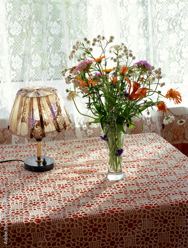 Rustic still life with the vase of summer flowers and the vintage table lamp. Country postcard. Greeting card. vertical