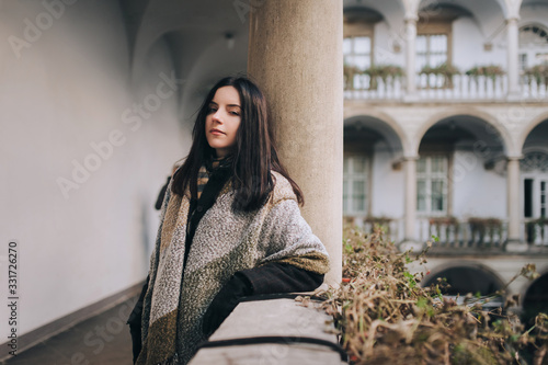 Tableau sur Toile A young black-haired girl in a dark autumn coat and a wide scarf-wrap stands on the balcony with a colonnade and looks looking at the viewer