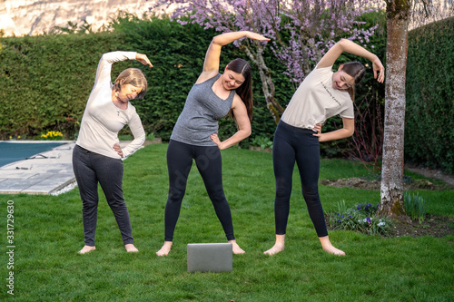 Obraz Family practicing fitness lesson online outdoors in garden at quarantine isolation period during coronavirus pandemic. Doing sport together at home via skype. Healthy active lifestyle - fototapety do salonu