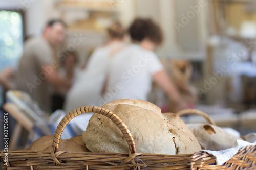cesta con pan en taller de elaboración con gente al fondo Canvas Print