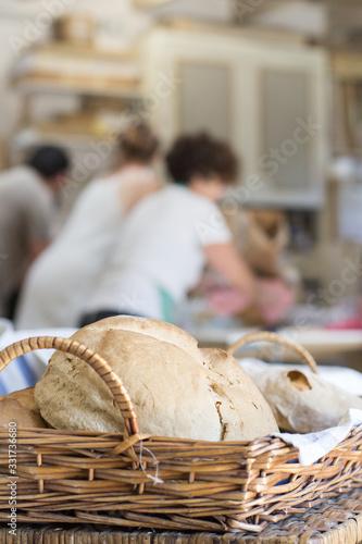 Photo cesta con pan en taller de elaboración con gente al fondo