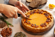 Man Cuts A Piece Of Pumpkin Pie And Puts It On A Plate. Autumn Family Dinner. Homemade Sweet Cake. Traditional Festive Dessert.