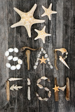 Seashell, Driftwood And Pebble Abstract Forming The Word Starfish On Rustic Wood Background.