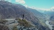 Lone man standing on high cliff at edge of abyss above deep mountain river gorge