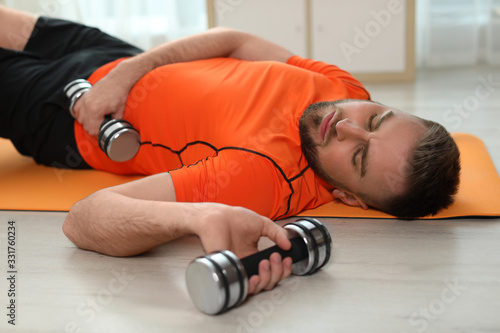 Obraz Lazy young man with sport equipment on yoga mat at home - fototapety do salonu