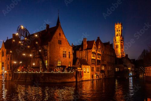 Fototapeta Brujas de noche con una de sus torres medievales y un canal en primer plano obraz na płótnie