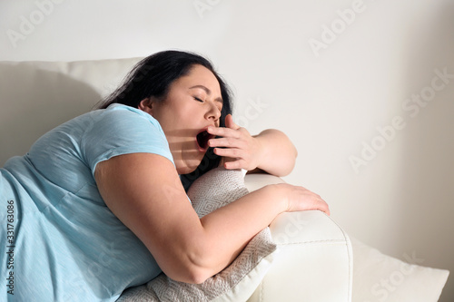 Lazy overweight woman resting on sofa at home Canvas Print