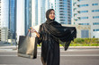 Leinwanddruck Bild - Beautiful middle eastern woman in abaya holding shopping bags on city street