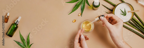 Canvastavla Pipette with CBD cosmetic oil in female hands on a table background with cosmeti
