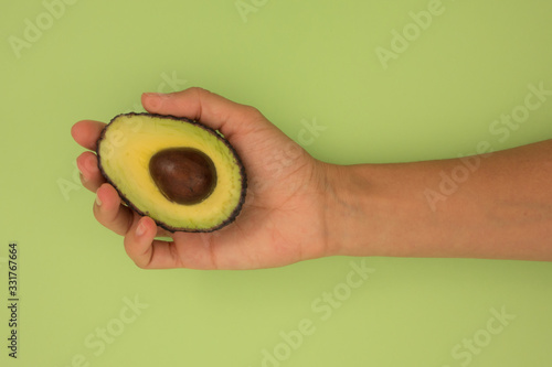 Hand holding half avocado on green background. Canvas Print
