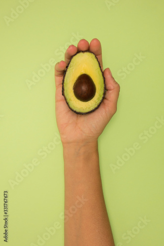 Hand holding half avocado on green background. Wallpaper Mural
