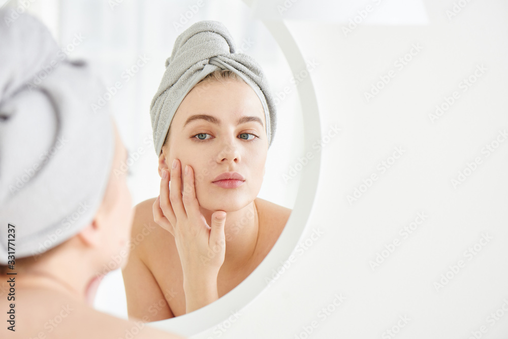 Fototapeta Portrait of  young girl with  towel on head in white bathroom looks and touches her face in the mirror and enjoys youth and hydration. Natural beauty, home care for problem skin