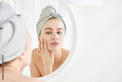 Fotografia Portrait of  young girl with  towel on head in white bathroom looks and touches her face in the mirror and enjoys youth and hydration