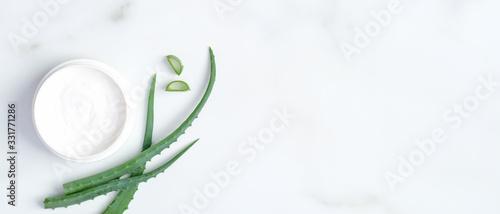 Fototapeta Natural cosmetic skincare moisturizer cream jar and sliced stems aloe vera on marble background
