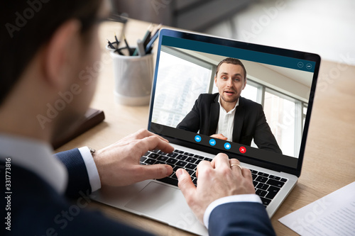 Fototapeta Pc screen view over businessman shoulder, due to corona virus all communications, business negotiations, perform distantly via videoconference, to exclude risk of infection outbreak and spread concept obraz