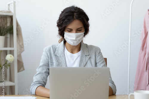 Obraz Young business woman wearing face mask working on computer seated at workplace desk in office room protecting herself from getting grippe vs COVID-19 corona virus pandemic infectious disease concept - fototapety do salonu