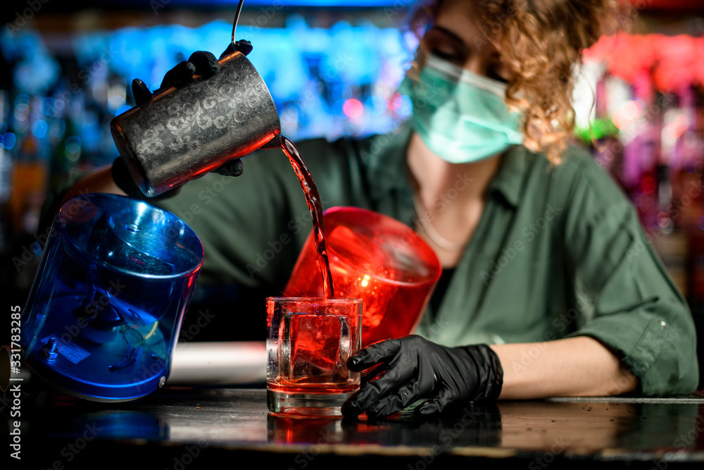 Fototapeta Young bartender girl in medical mask and black gloves professionally pour drink from steel glass into glasses with ice.