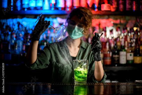 Obraz young girl at bar counter in medical mask and black gloves accurate holds glass and spray to it. - fototapety do salonu