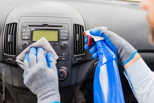 Obraz Man cleansing car dashboard and spraying with disinfection liquid. - fototapety do salonu