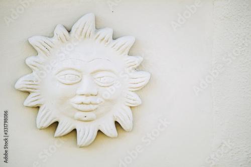Photo Sculpture soleil et visage sur la façade d'une maison