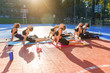 canvas print picture - Fitness team of likable sporty slender women doing yoga exercises lying on special mats on the outdoor stadium in the urban green park