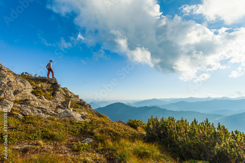 Hiker or tourist admiring the beautiful mountain landscape at sunset Canvas Print