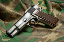 Belgian Made Browning Hi-Power 9mm Semiautomatic Handgun With Wood Checkered Grips And Tangent Rear Sight Against A Geen Camo Background