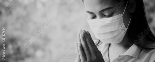 Fotografia, Obraz Thai woman wearing a mask to protect the virus, Covid 19 Praying for blessings from God for the world to be safe from this epidemic